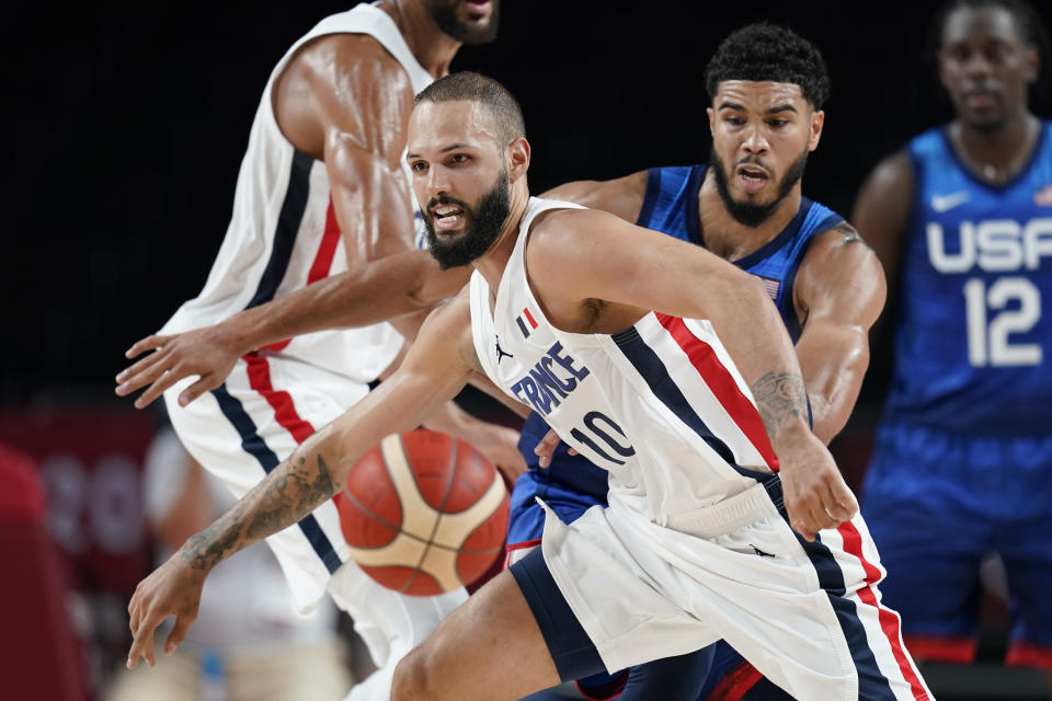 France's Evan Fournier (10) runs down a loose ball ahead of United States' Jayson Tatum, rear, during a men's basketball preliminary round game at the 2020 Summer Olympics, Sunday, July 25, 2021, in Saitama, Japan. (AP Photo/Charlie Neibergall)