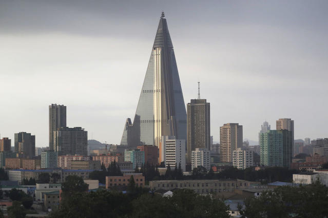 <p>The sky is overcast at the end of a workday on July 17, 2017, in Pyongyang, North Korea, where the 105-story pyramid-shaped Ryugyong Hotel is seen in this photograph towering over residential apartments. (Photo: Wong Maye-E/AP) </p>