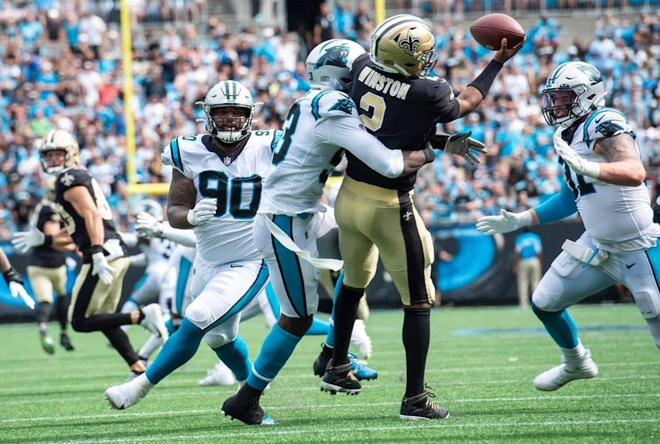 Panthers defensive end Brian Burns, center, wraps his arms around Saints quarterback James Winston during the game at Bank of America Stadium on Sunday. The Panthers defeated the Saints 26-7.