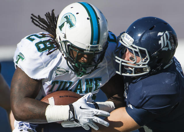Tulane running back Rob Kelley (28) is stopped for a loss by Rice safety Paul Porras (24) during the first quarter of an NCAA college football game at Rice Stadium, Saturday, Nov. 30, 2013, in Houston. (AP Photo/Houston Chronicle, Smiley N. Pool)
