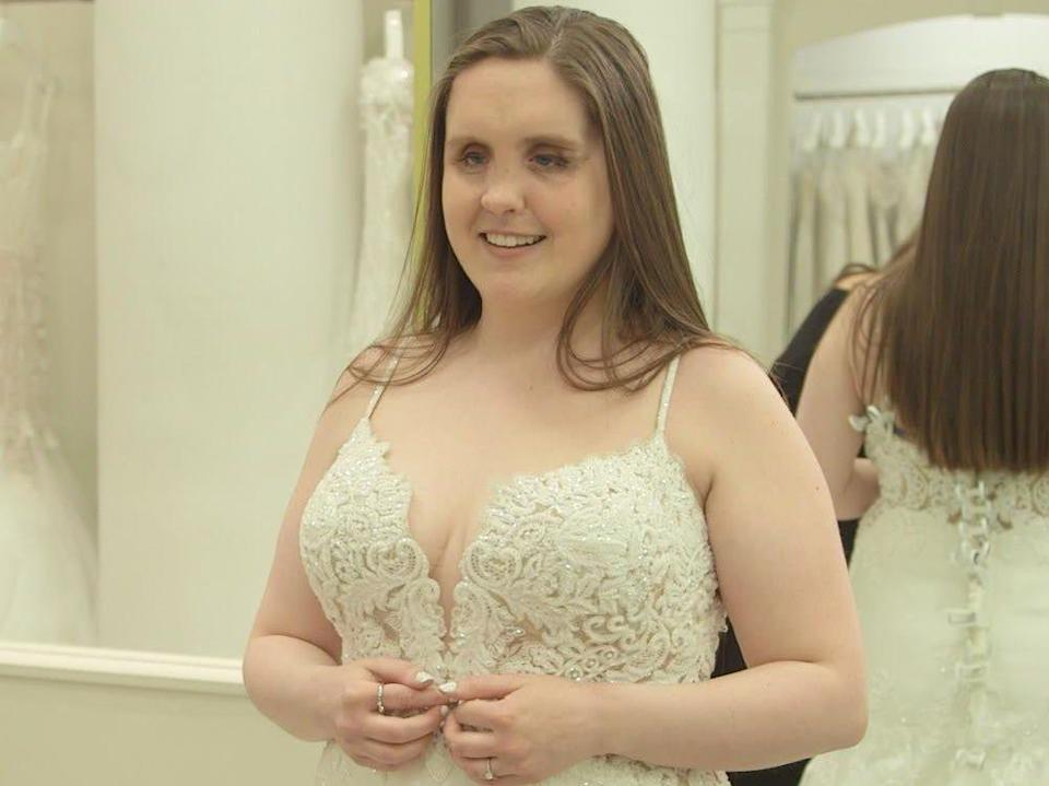 A bride with brown hair stands in Kleinfeld Bridal in a wedding dress.