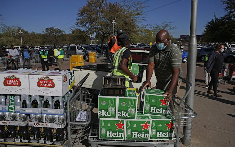 Workers help a customer load alcohol in to his van in Pretoria - PHILL MAGAKOE/AFP