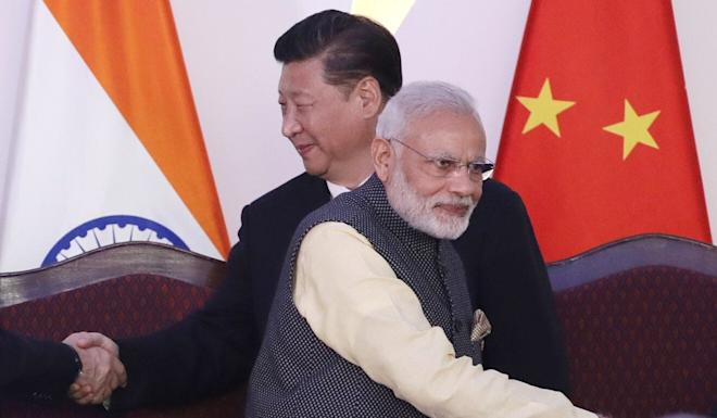 Under President Xi Jinping (pictured with Indian Prime Minister Narendra Modi) China is seeking to redraw its land and sea frontiers, academic Brahma Chellaney says. Photo: AP