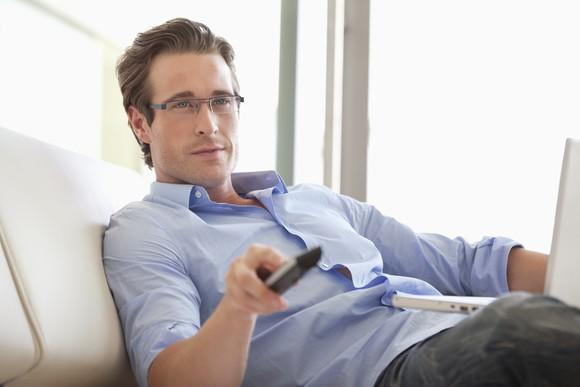 A man with a remote control and a laptop while watching TV on a couch.