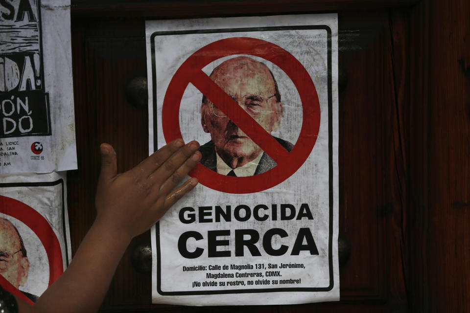"""A protester places a poster with a message that reads in Spanish, """"Genocide near you,"""" with an image of former Mexican President Luis Echeverría, on the front gate of his residence, during a march to commemorate the 50th anniversary of the student massacre of 1971 known as """"El Halconazo,"""" in Mexico City, Thursday, June 10, 2021. The attack, also known as the Corpus Christi massacre, was carried out by a group of men apparently recruited by the government to dissolve a pro-democracy student demonstration. (AP Photo/Marco Ugarte)"""