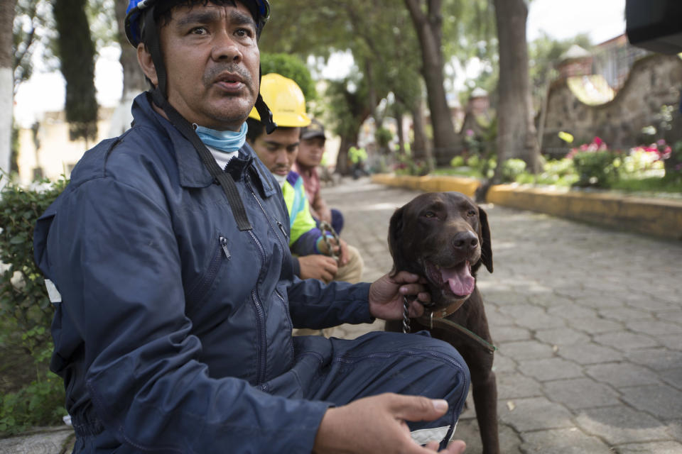 <p>Rescuer Ricardo Canseco Rodriguez and his dog Rocco rest during a break in search and rescue operations in San Gregorio Atlapulco, Mexico, Friday, Sept. 22, 2017. Mexican officials are promising to keep up the search for survivors as rescue operations stretch into a fourth day following Tuesday's major earthquake that devastated Mexico City and nearby states. (AP Photo/Moises Castillo) </p>
