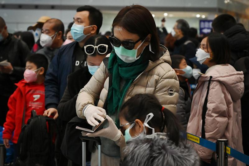 A woman wears a protective face mask and gloves while waiting to go through immigration at Beijing airport.