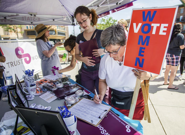 FILE - In this July 9, 2016 file photo, Community member Megan Wright-Hagan signs a form at the Trust Women booth during the Reproductive Rights Repro Rally held at the Old Town Square in downtown Wichita, Kan. Even before a strict abortion ban took effect in Texas this week, clinics in neighboring states were fielding more and more calls from women desperate for options. (Manny De Los Santos/Wichita Eagle via AP)