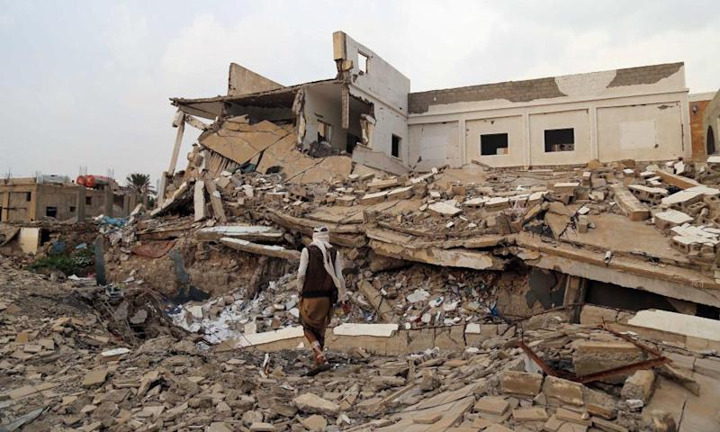A man walks past a destroyed school in Yemen