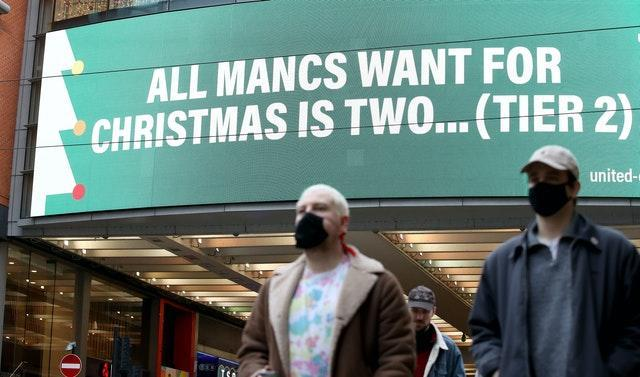 People wearing face masks walk past a sign on Market Street, Manchester