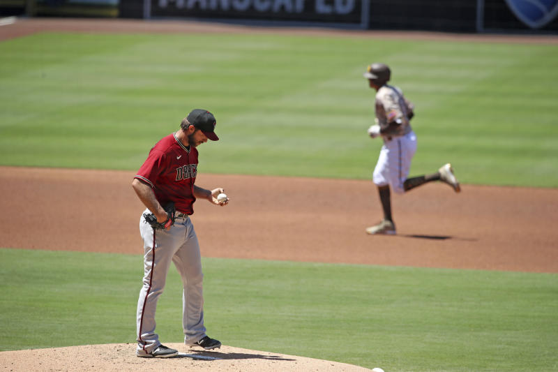 Madison Bumgarner in a red jersey holding a ball on the mound while Manny Machado jogs to second behind him.