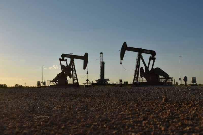 Pump jacks operate in front of a drilling rig in an oil field in Midland