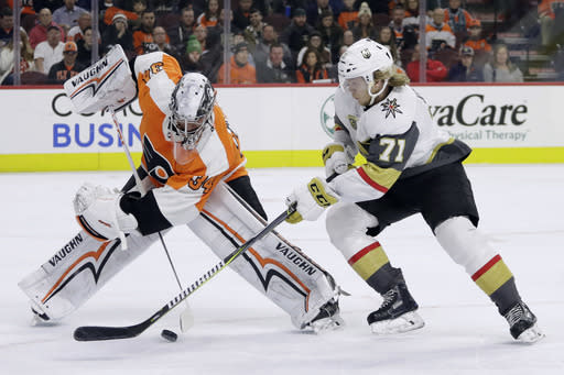 Philadelphia Flyers' Petr Mrazek, left, and Vegas Golden Knights' William Karlsson battle for the puck during the first period of an NHL hockey game, Monday, March 12, 2018, in Philadelphia. (AP Photo/Matt Slocum)