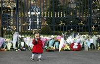 Maisie Cairns (18 months) stands at the gates of Hillsborough Castle in Belfast, Northern Ireland, Saturday, April 10, 2021. People gathered to pay respect to Britain's Prince Philip who died early Friday. Prince Philip, the irascible and tough-minded husband of Queen Elizabeth II who spent more than seven decades supporting his wife in a role that both defined and constricted his life. (AP Photo/Peter Morrison)