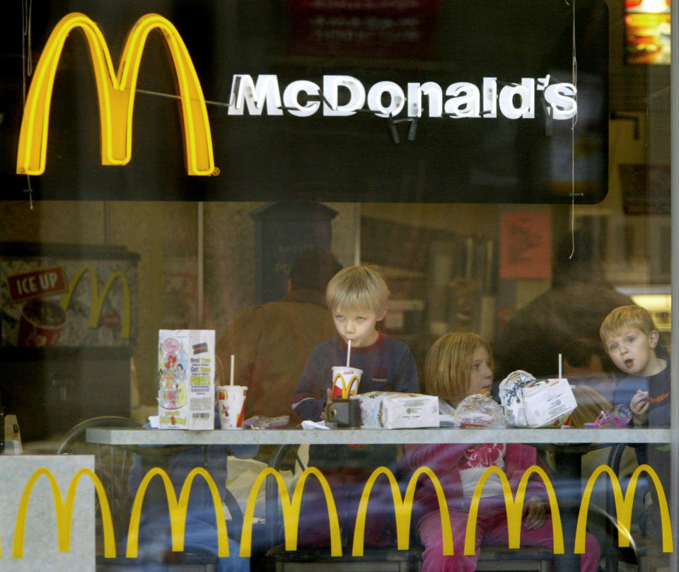 Children peer out the window while eating hamburgers in a Chicago McDonald's restaurant, December 26, 2003. The U.S. Agriculture Department said on Friday it quarantined a second herd in Washington state as part of its investigation into the nation's first case of mad cow disease. Restaurant shares edged higher after sliding earlier this week on fears that consumers will shy away from beef because of of the mad cow case. McDonald's gained 13 cents to $24.09. CPROD REUTERS/John Gress  JG/GN