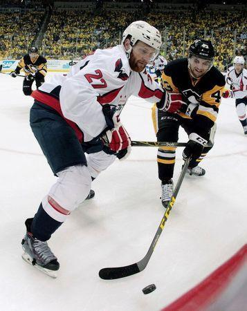 Washington Capitals defenseman Karl Alzner (27) and Pittsburgh Penguins left wing Conor Sheary (43) fight for the puck along the boards during the second period in game three of the second round of the 2016 Stanley Cup Playoffs at the CONSOL Energy Center. The Pens won 3-2. Mandatory Credit: Charles LeClaire-USA TODAY Sports