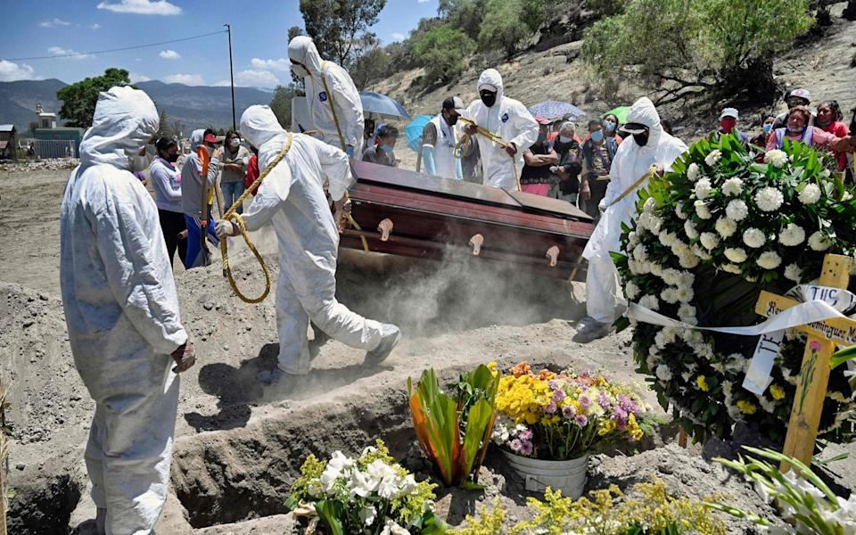 Workers bury an alleged victim of Covid-19 at the Municipal Pantheon of Valle de Chalco, in Mexico - ALFREDO ESTRELLA/AFP