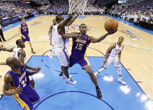 Los Angeles Lakers forward Metta World Peace (15) shoots in front of Oklahoma City Thunder forward Serge Ibaka, center left, during the first quarter in Game 2 of an NBA basketball playoffs Western Conference semifinal, in Oklahoma City on Wednesday, May 16, 2012. (AP Photo/Sue Ogrocki)