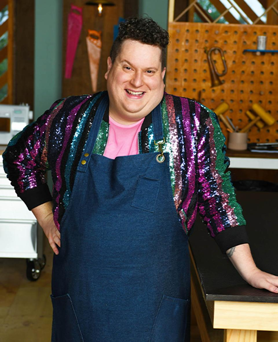 Making It contestant Russell posing on set wearing a purple, blue and green striped sequin jacket and a denim apron