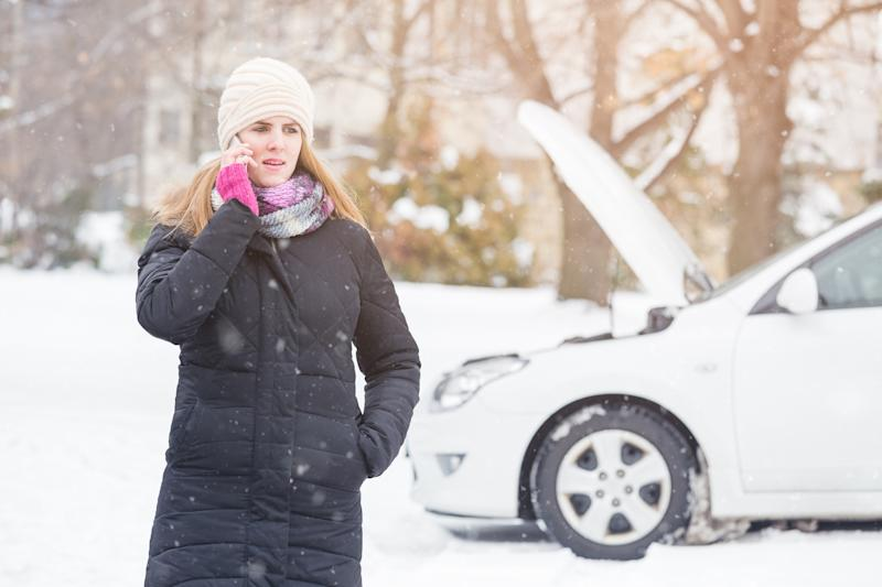 Woman in coat on phone in front of white car with its hood up
