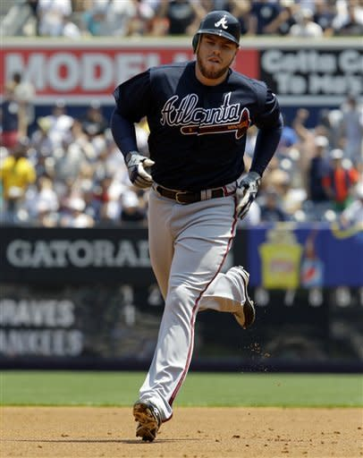 Atlanta Braves' Freddie Freeman trots around the bases after hitting a two-run home run off New York Yankees starting pitcher Phil Hughes during first inning of a baseball game at Yankee Stadium in New York, Wednesday, June 20, 2012. (AP Photo/Kathy Willens)