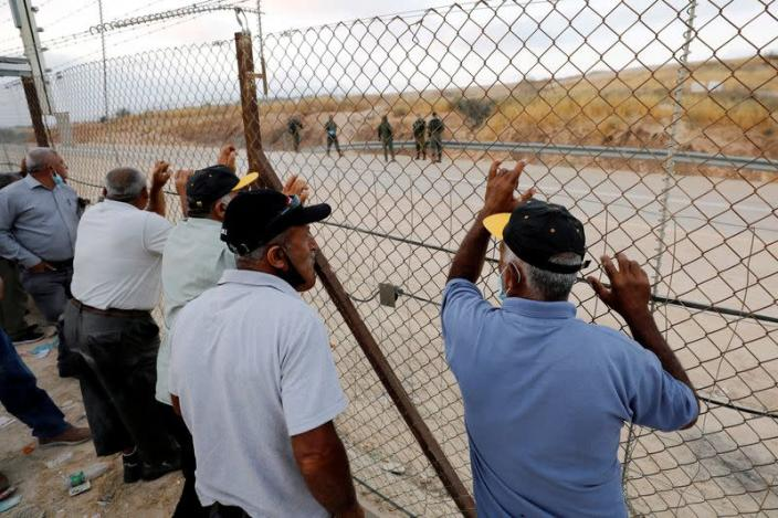 FILE PHOTO: Palestinian laborers gather near an Israeli checkpoint closed amid fears of a second wave of COVID-19 infections, near Hebron