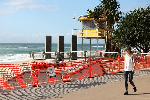 A woman walks past a closed Surfers Paradise beach.