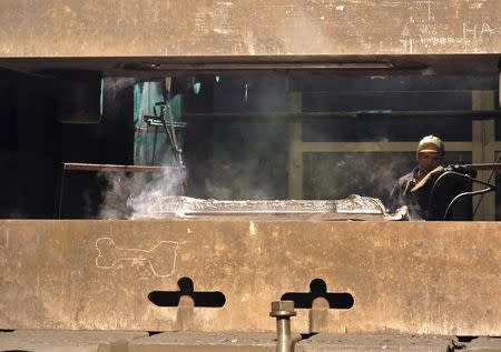 An employee works with a titanium ingot at the VSMPO-Avisma factory in Verkhnyaya-Salda, some 1,800 km (1,100 miles) east of Moscow, in this November 7, 2013 file photo. REUTERS/Svetlana Burmistrova/Files