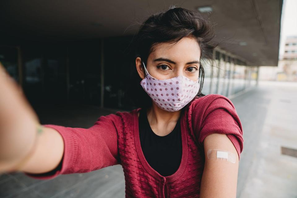 Millennial mixed race woman taking a selfie after her Covid-19 vaccination.