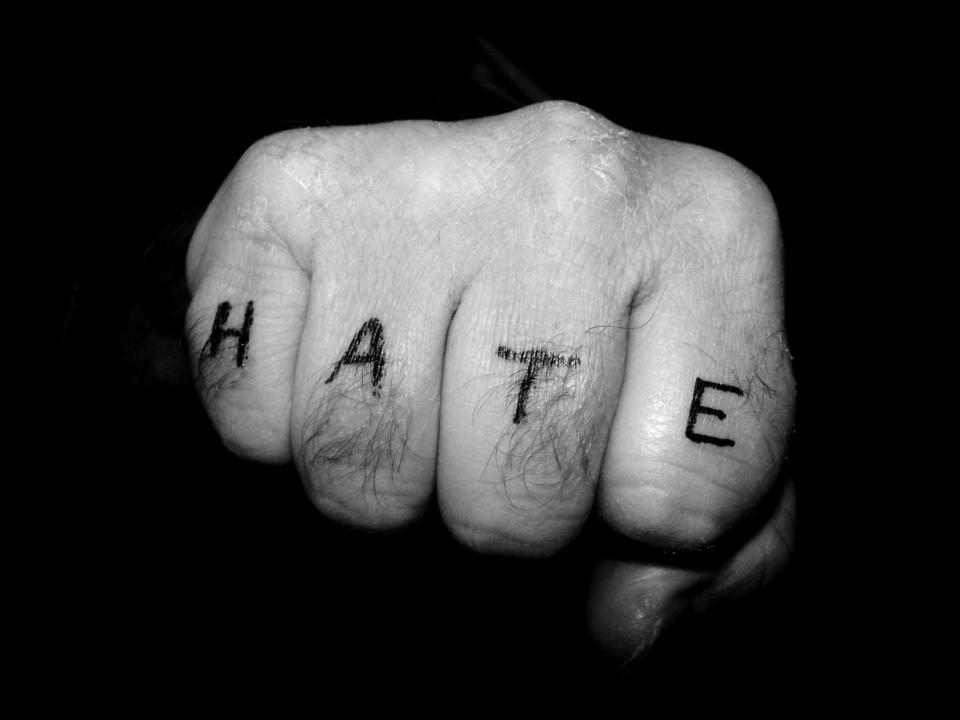 A fist with the word HATE written on the fingers.