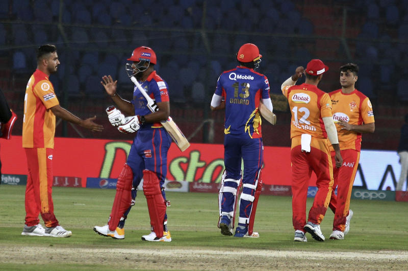 Karachi Kings players Umaid Asif, center, and Chris Jordan, second left, shake hand with Islamabad United players on the end of their Pakistan Super League T20 cricket match at the National Stadium in Karachi, Pakistan, Saturday, March 14, 2020. (AP Photo/Fareed Khan)