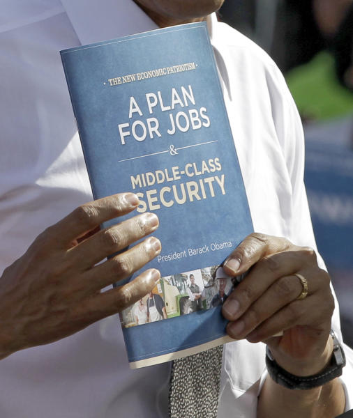 President Barack Obama holds a copy of his plan for jobs pamphlet while speaks to supporters, where he layed out his plan to move the country forward, Tuesday, Oct. 23, 2012, during a campaign stop in Delray Beach, Fla. (AP Photo/Alan Diaz)