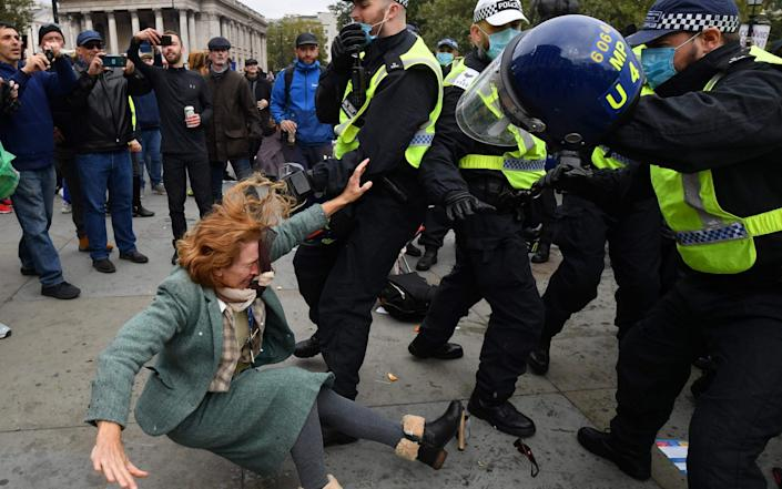A woman falls as police move in to disperse protesters in Trafalgar Square - JUSTIN TALLIS/AFP