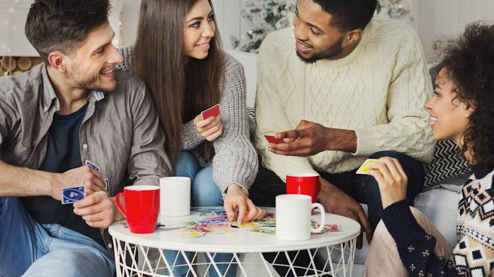 Multiracial friends having fun and playing game of cards UNO against christmas tree.