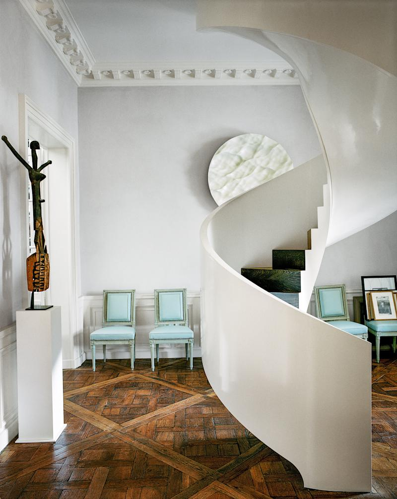 A sculptural spiraling staircase connects Grange's original flat to the apartment above.