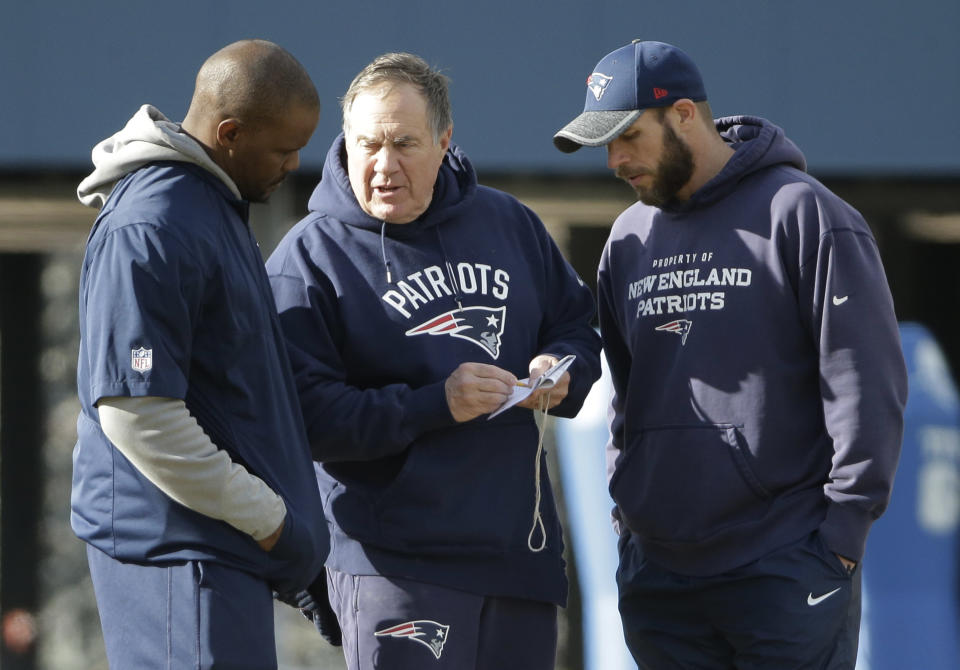Linebackers coach Brian Flores (left) shares plans with head coach Bill Belichick (middle) and defensive line coach Brendan Daly at a January practice. (AP)