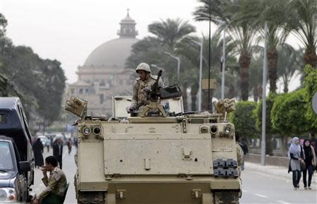 A soldier sits on guard atop an armoured personnel carrier at the main gate of the Cairo University around Al Nahda in Cairo