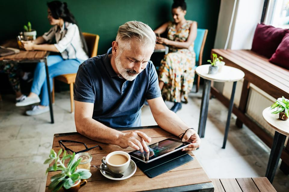 A mature man using a digital table in a cafe while he relaxes with a cup of coffee.