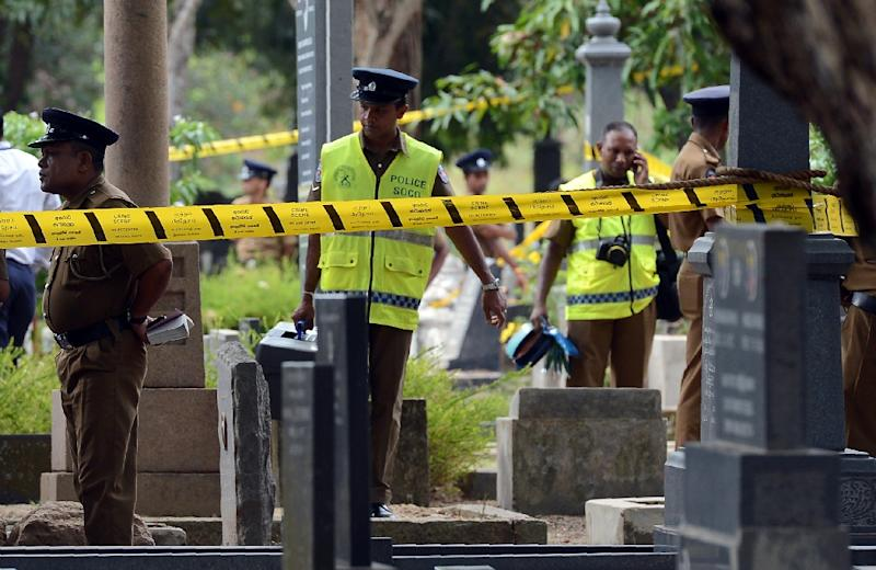 Sri Lankan police officials stand near the grave of anti-establishment newspaper editor Lasantha Wickrematunga as his body is exhumed at a cemetery in Colombo on September 27, 2016 (AFP Photo/Lakruwan Wanniarachchi)