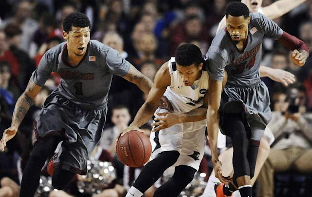 Massachusetts' Maxie Esho, left, and Raphiael Putney, right, pressure Providence's Josh Fortune, center, during the first half of an NCAA college basketball game, Saturday, Dec. 28, 2013, in Amherst, Mass. (AP Photo/Jessica Hill)