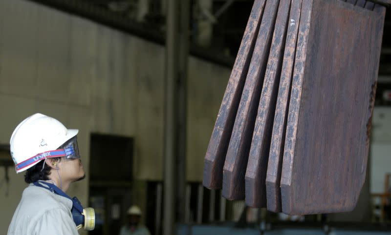 FILE PHOTO: A worker monitors the loading of copper plates at PT Smelting in Gresik
