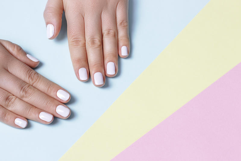 Female hand with white manicure on a on pastel colored background with copy space, top view