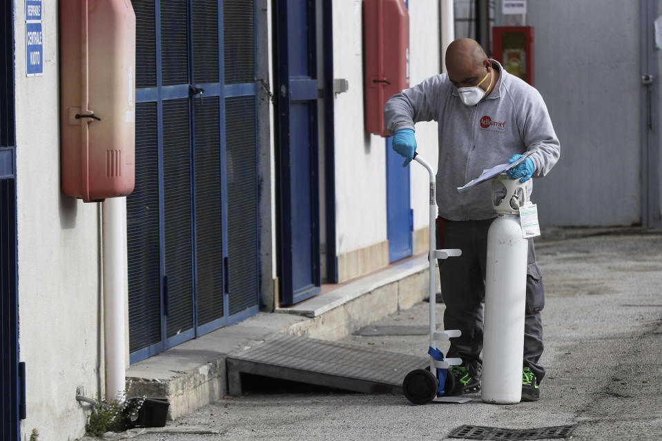 A man loads an oxygen canister near the first aid department of the San Giuliano hospital in Giugliano in the outskirts of Naples, Italy, Saturday, Nov. 14, 2020. The pandemic has heightened the urgency of the plight of those seeking medical care in public hospitals in Italy's economically under-developed south. (AP Photo/Gregorio Borgia)