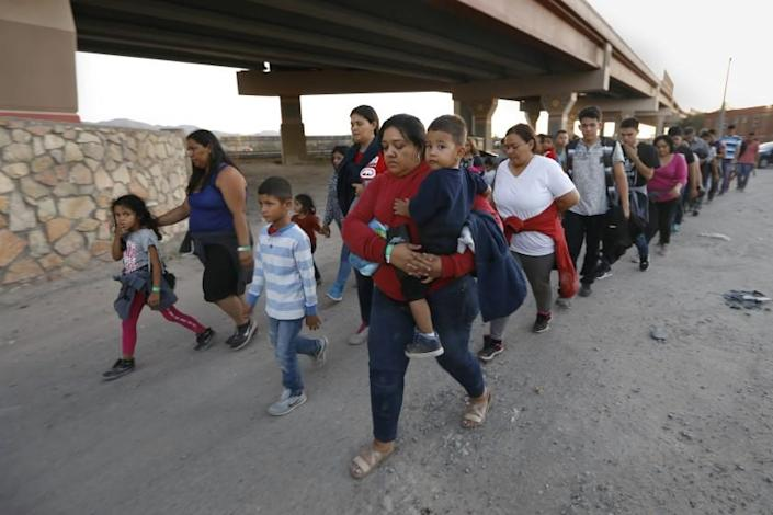 EL PASO, TEXAS--JUNE 21, 2019--A group of about 50 men, women and children are led by U.S. border patrol agents and police to a holding area after they crossed into the U.S. to seek asylum on Wednesday, June 19, 2019. Texas is sending an additional 1,000 Nation Guard troops to the border to help with the increase in migrant families crossing the border and asking for asylum. Despite the border wall and wire, there is a gap in the wall in downtown El Paso that makes entry easy. It also funnels the migrants to an area where U.S border patrol agents can take them into custody. With the Rio Grande River at a very low level, a large group of migrants crosses from Juarez, Mexico to El Paso, Texas with little effort. (Carolyn Cole/Los Angeles Times)