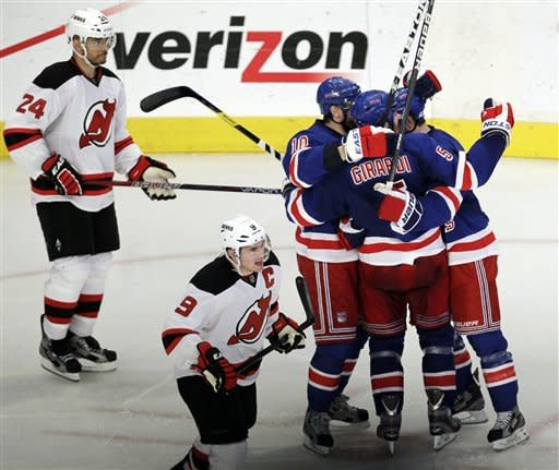 New York Rangers players celebrate a goal scored by Dan Girardi (5) as New Jersey Devils' Bryce Salvador (24) and Zach Parise (9) skate by during the third period of Game 1 of their NHL hockey Stanley Cup Eastern Conference final playoff series, Monday, May 14, 2012, at New York's Madison Square Garden. (AP Photo/Julio Cortez)
