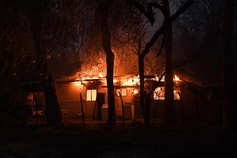 Engulfed: Firefighters investigate a blazing building (AFP/Getty Images)