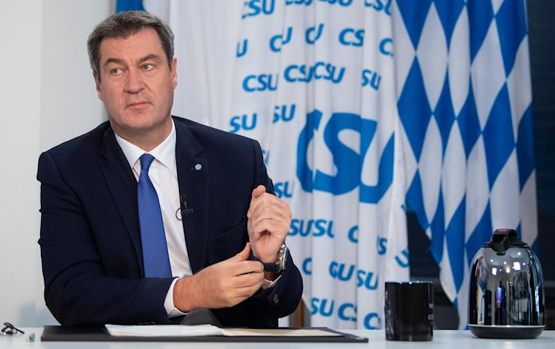 """26 September 2020, Bavaria, Munich: Markus Söder (CSU), party chairman and Minister President of Bavaria, is sitting in his office in the CSU state leadership before his speech at the virtual party conference. On his desk is a mug with the inscription """"Winter is coming/Winter is here"""" and a motif from the television series """"Game of Thrones"""". The participants of the party conference can follow the speech in a stream. This is already the second party conference that the CSU has held only on the Internet since the beginning of the Corona pandemic. Photo: Sven Hoppe/dpa (Photo by Sven Hoppe/picture alliance via Getty Images)"""