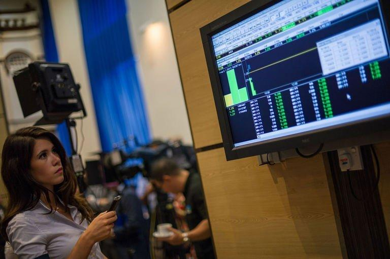 A woman looks at a digital display showing share prices after the listing debut of AirAsia X at Malaysia Stock Exchange in Kuala Lumpur on July 10, 2013. Shares in AirAsia X rose 1.60 percent on their market debut in Malaysia as the firm's chief executive promised a spending spree on new planes to boost frequency and target more routes
