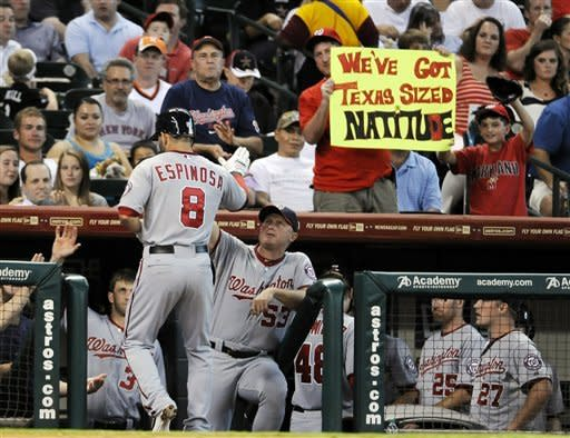 Washington Nationals' Danny Espinosa (8) is welcomed back to the dugout by bench coach Randy Knorr (53) and fans after hitting a two-run home run against the Houston Astros in the second inning of a baseball game, Tuesday, Aug. 7, 2012, in Houston. (AP Photo/Pat Sullivan)