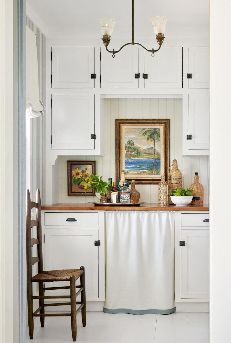 <p>In small kitchens or pantries, hefty stainless steel appliances tend to overpower the room. An easy fix (for ice makers or sinks needing hidden storage) is a simple skirt, like the blue-trimmed one here. You can easily replicate this look with just a yard of fabric and a tension rod.</p>